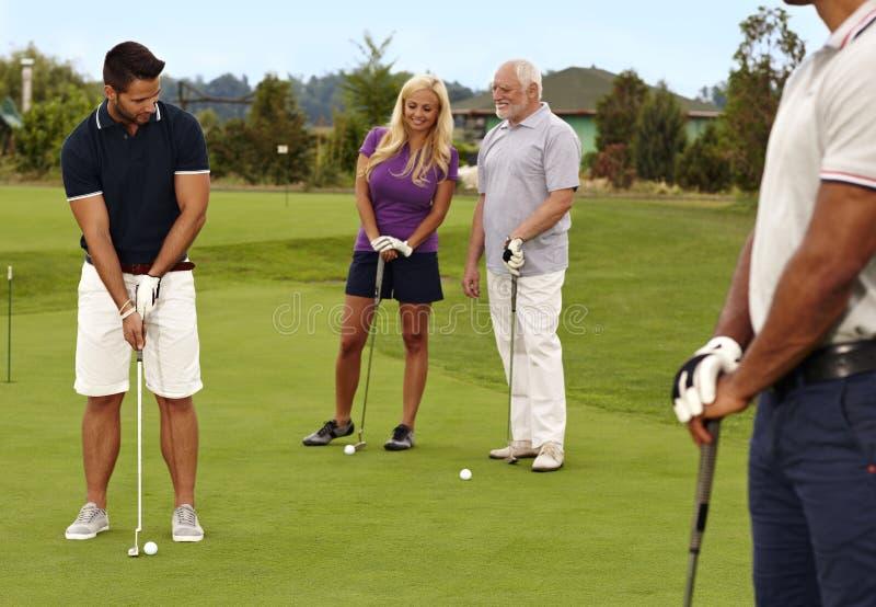 Jogadores de golfe que jogam no verde imagens de stock royalty free