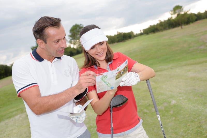 Jogadores de golfe que leem o mapa foto de stock
