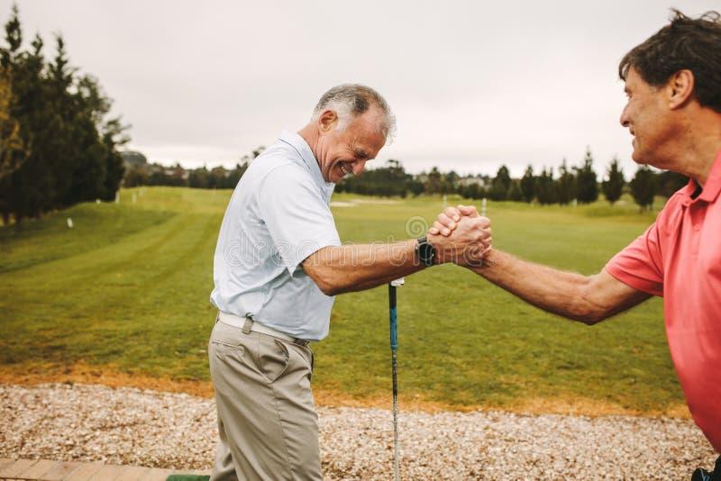 Jogadores de golfe superiores que apreciam no driving range do golfe fotos de stock royalty free