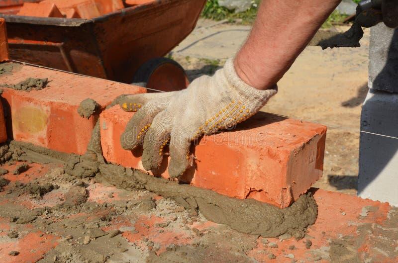 Jogadores de tijolos mãos em luvas de alvenaria parede de alvenaria Bricklay, Masonry, Brickwork close imagem de stock royalty free