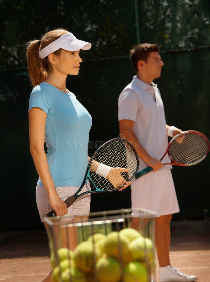 Jogadores novos na corte de tênis imagens de stock
