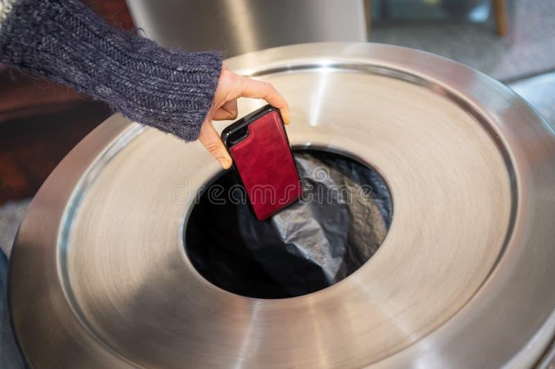 Jogando afastado o telefone celular no escaninho dos desperdícios fotos de stock