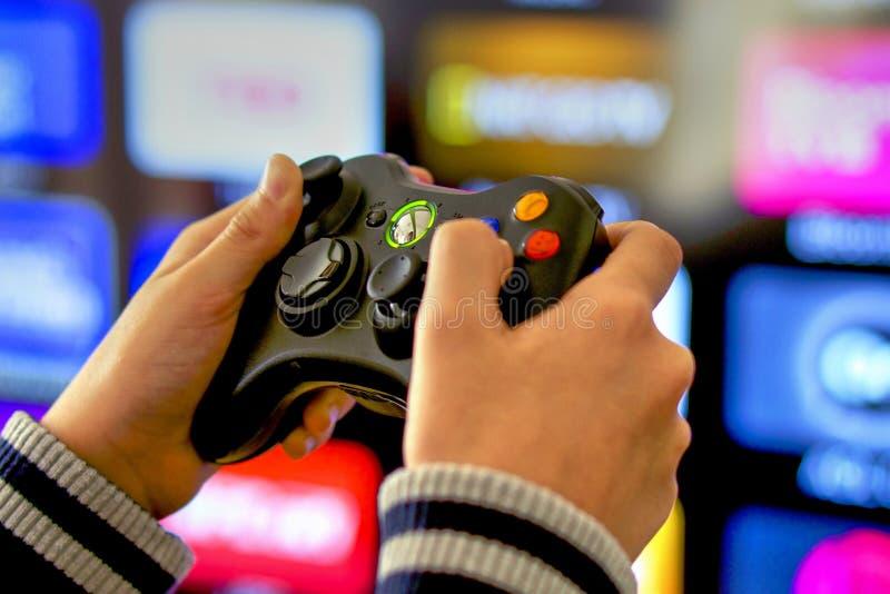 Jogando jogos de vídeo no console de Xbox, fundo da tevê foto de stock