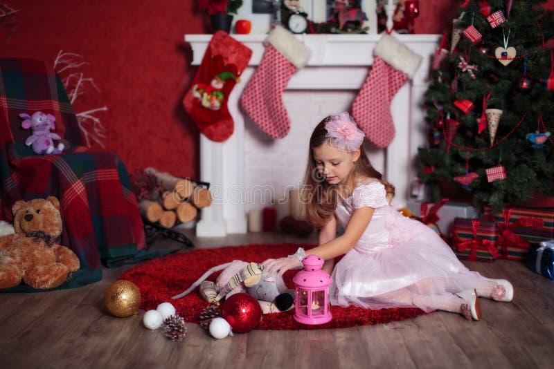 Jogando a menina perto da árvore de Natal imagens de stock royalty free