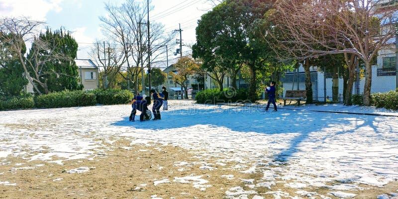 Jogando a neve antes que se acabar imagens de stock