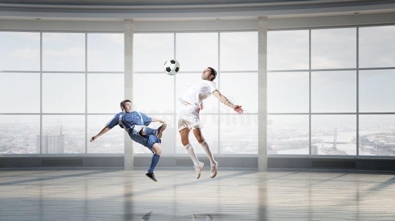 Jogando o futebol no escritório Meios mistos foto de stock royalty free