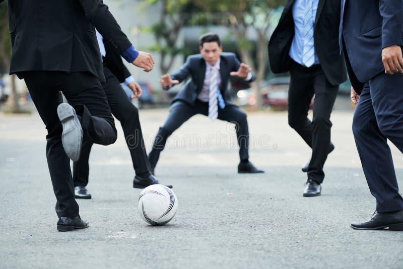 Jogando o futebol no hora do almoço fotografia de stock royalty free