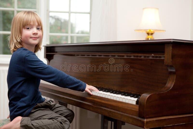Jogando o piano, instrumento da criança do menino foto de stock