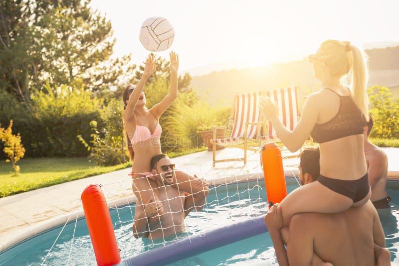 Jogando o voleibol em uma piscina foto de stock