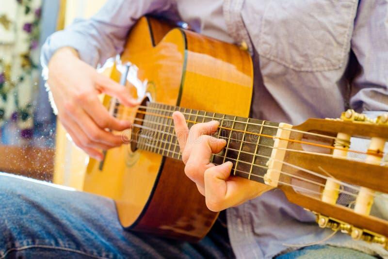 Jogando uma guitarra acústica fotos de stock royalty free