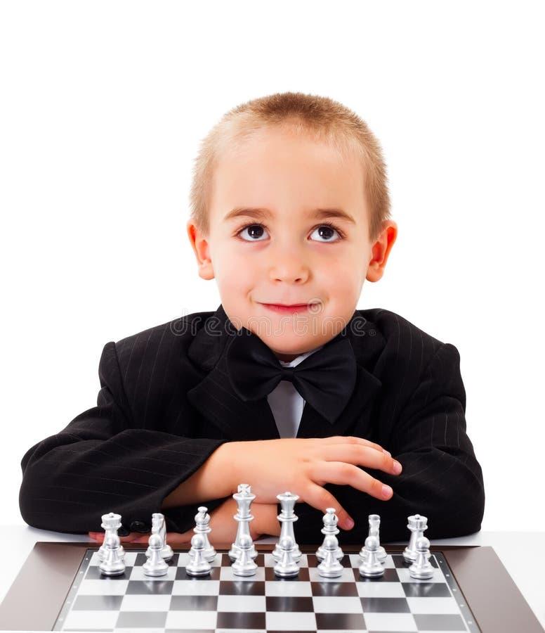 Jogando a xadrez com rapaz pequeno imagens de stock royalty free