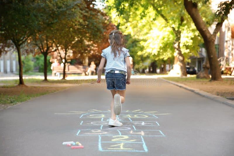 Jogar amarelinha da criança pequena tirado com giz colorido fotos de stock