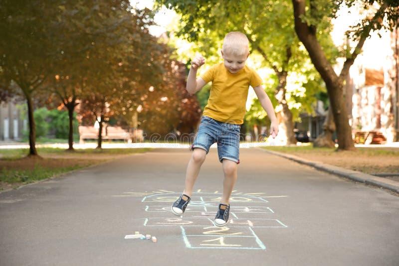 Jogar amarelinha da criança pequena tirado com giz colorido fotografia de stock royalty free