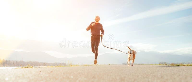 Jogga mannen med hans hund i morgonen Aktiv sund livsstilbegreppsbild fotografering för bildbyråer