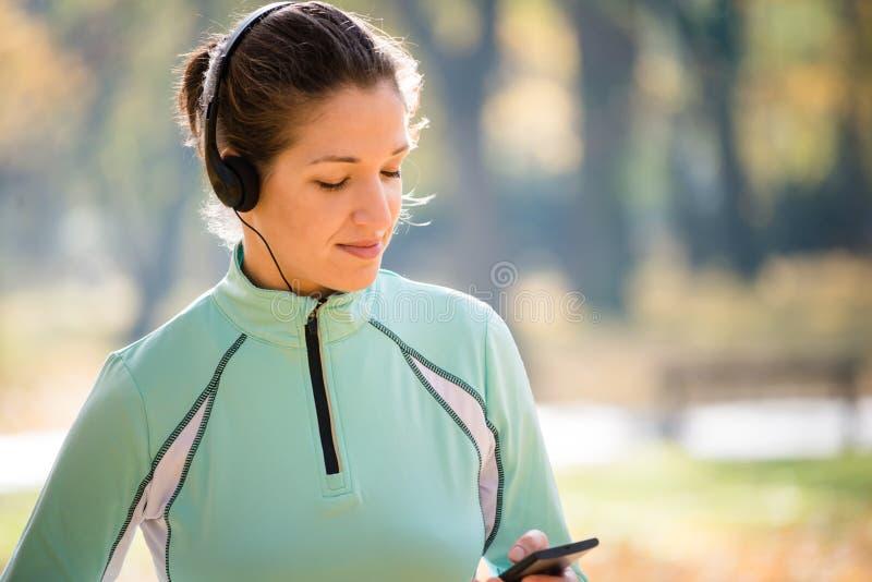 Jogga och lyssnande musik för kvinna royaltyfri bild