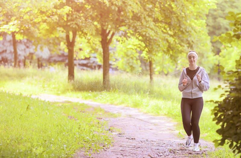Jogga sportbegrepp: Ung rinnande konditionkvinna som utbildar Outd royaltyfria foton