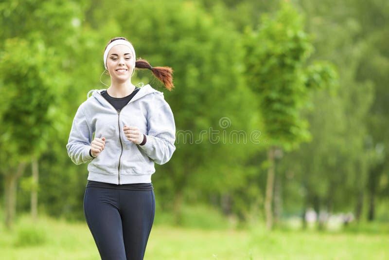 Jogga sportbegrepp: Ung rinnande konditionkvinna som utbildar Outd arkivfoto