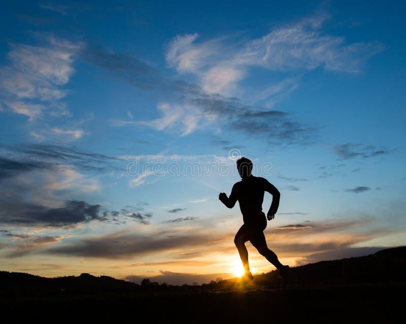 jogger ηλιοβασίλεμα σκιαγραφιών στοκ φωτογραφία