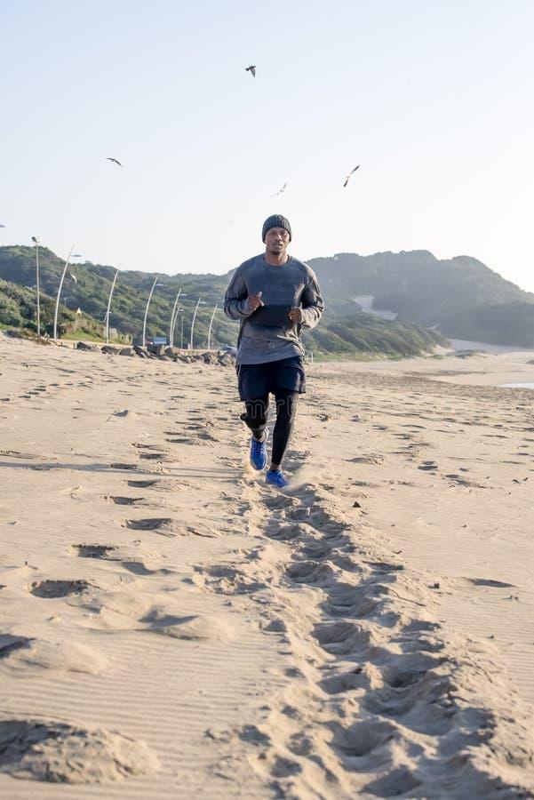 Jogger που πλησιάζει κατά μήκος της παραλίας στοκ εικόνα
