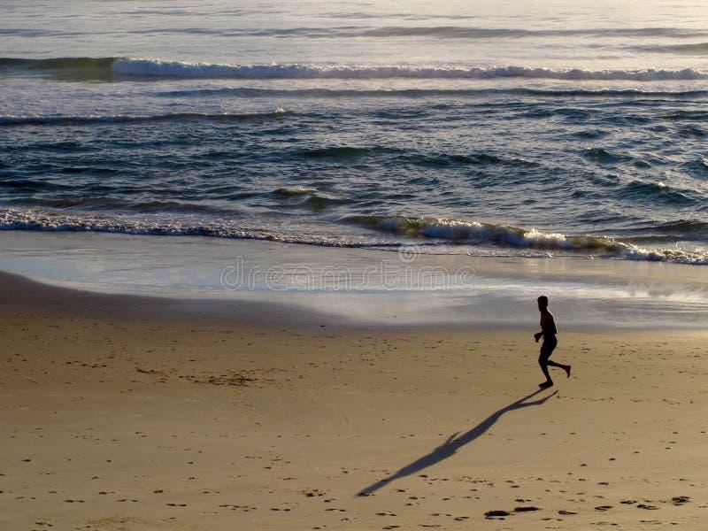 Jogger στην παραλία στην ανατολή στοκ εικόνες
