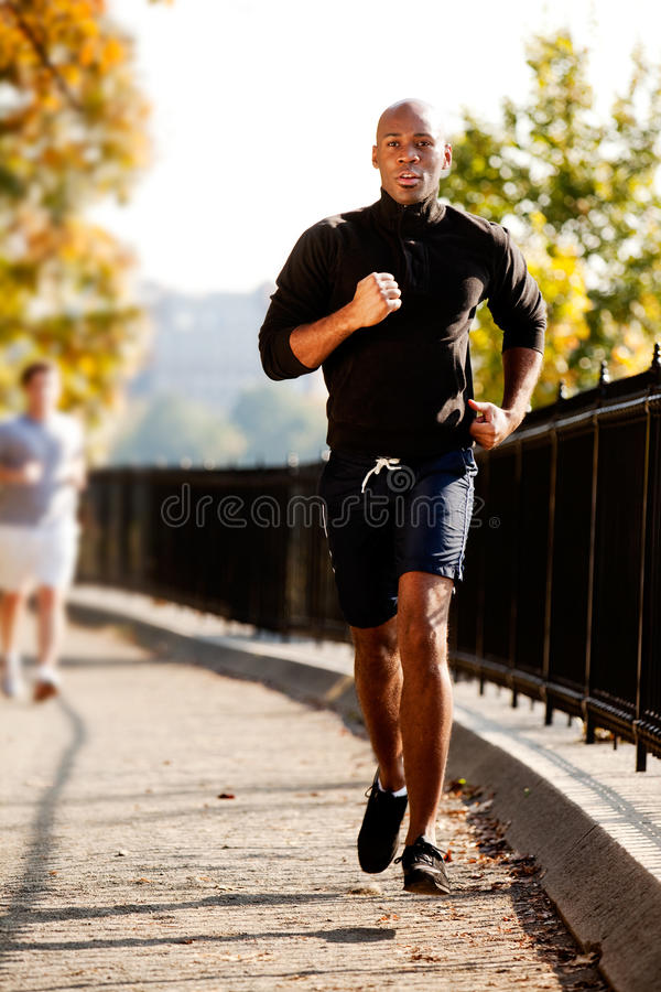 Jogger. An African American jogging in a park in the morning stock photos