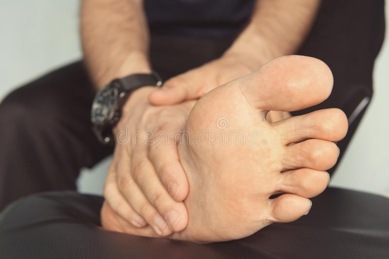 Jogger hands on foot. He is feeling pain as his ankle or foot is broken or twisted. Accident on running track during the morning royalty free stock photo