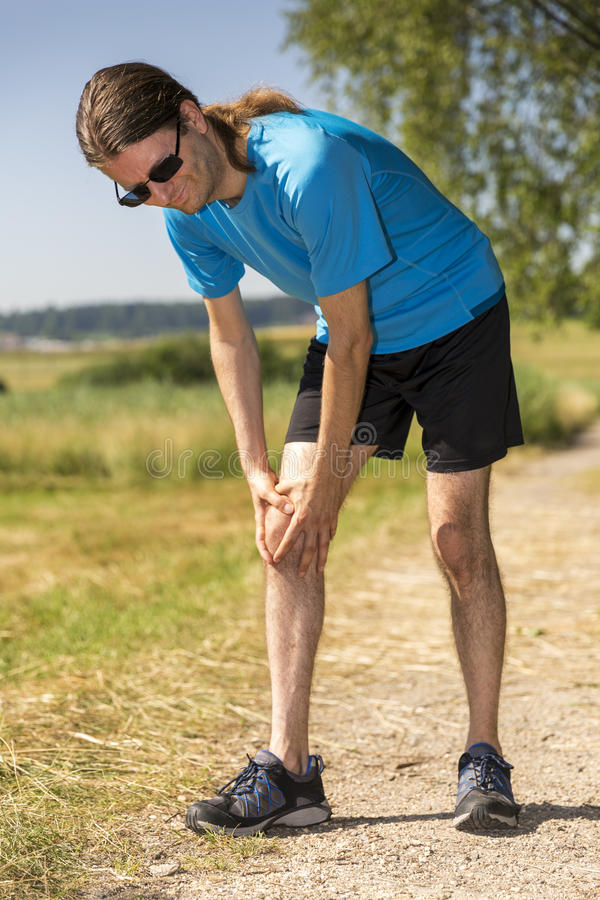 Jogger having a knee pain stock photos