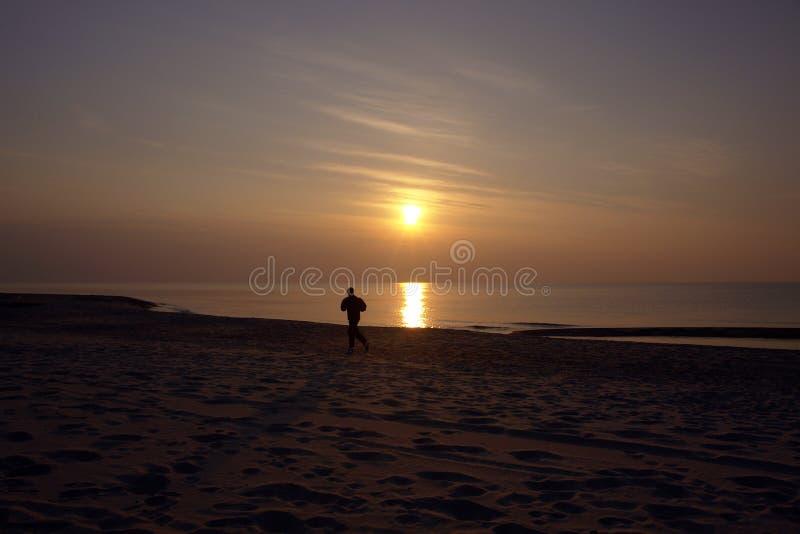 Jogger op strand stock foto's