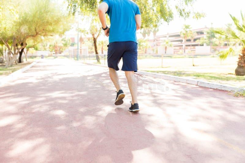 Jogger Opleiding op Voetpad tijdens Sunny Day In Park stock afbeeldingen