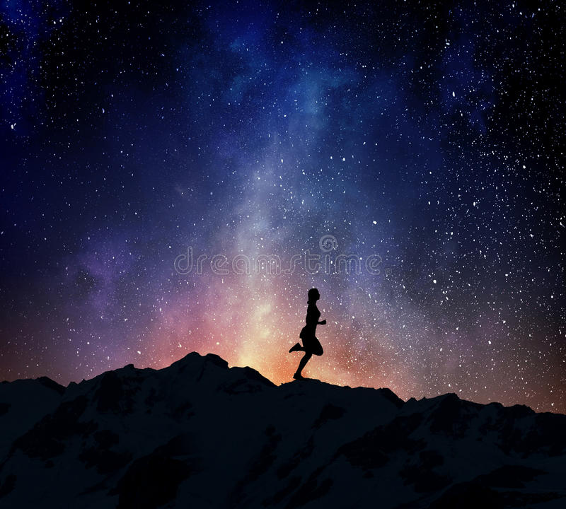 Jogger running at night . Mixed media. Silhouette of sport woman running against starry sky . Mixed media stock photo