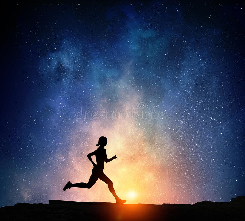 Jogger running at night . Mixed media. Silhouette of sport woman running against starry sky . Mixed media royalty free stock image