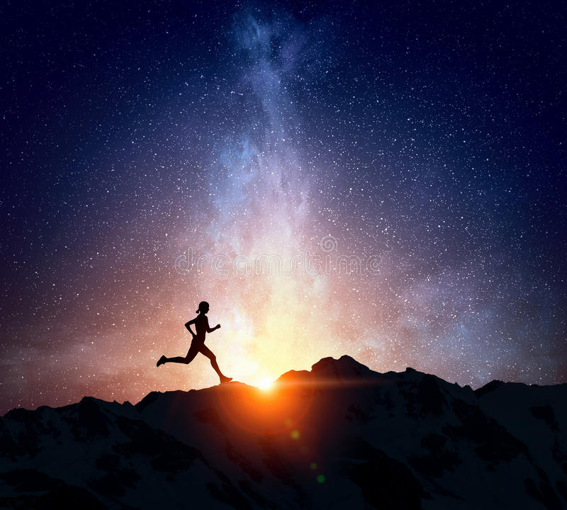 Jogger running at night . Mixed media. Silhouette of sport woman running against starry sky . Mixed media stock photography
