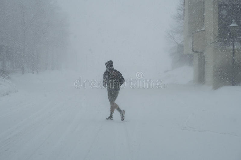 Jogger in Snow Storm. An jogger runs along the street in a winter snow storm in near whiteout winter conditions stock photo