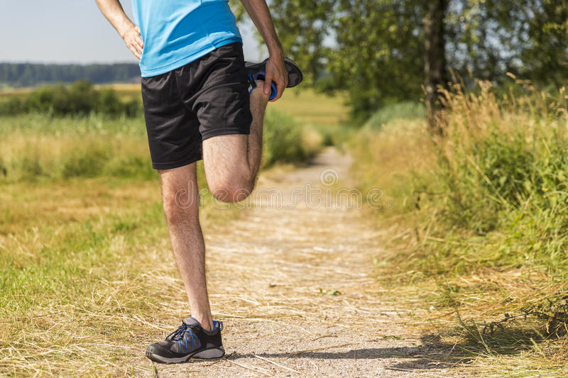 Jogger stretching his legs stock photos