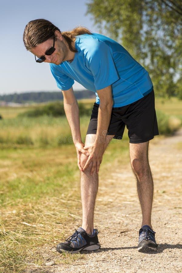Joggeren som har ett knä, smärtar arkivfoton