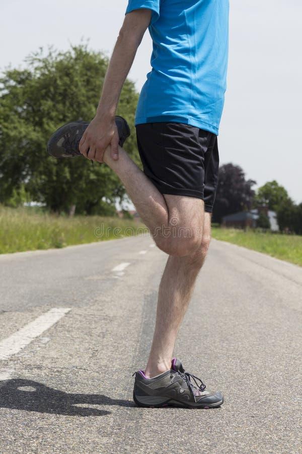 Joggerman som sträcker hans ben arkivfoton