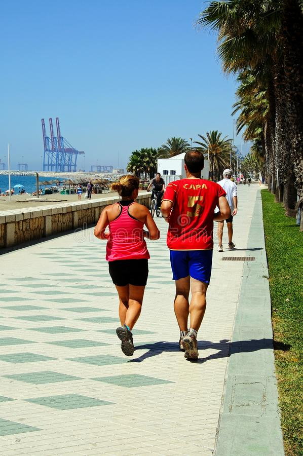 Joggers along promenade, Malaga. royalty free stock images