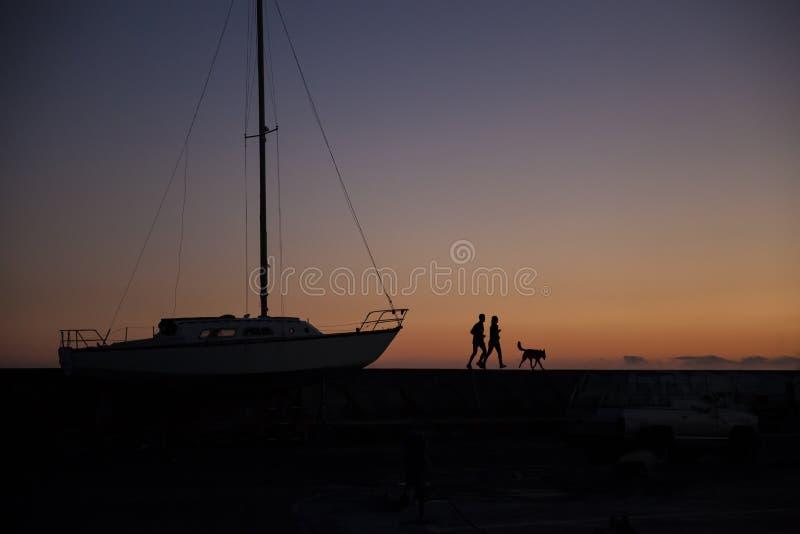 Joggers i solnedgång med fartyget royaltyfri fotografi