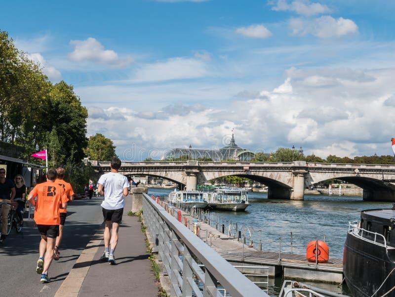 Joggers kör på Berges de Seine med Seine River och tusen dollar Palais royaltyfri fotografi