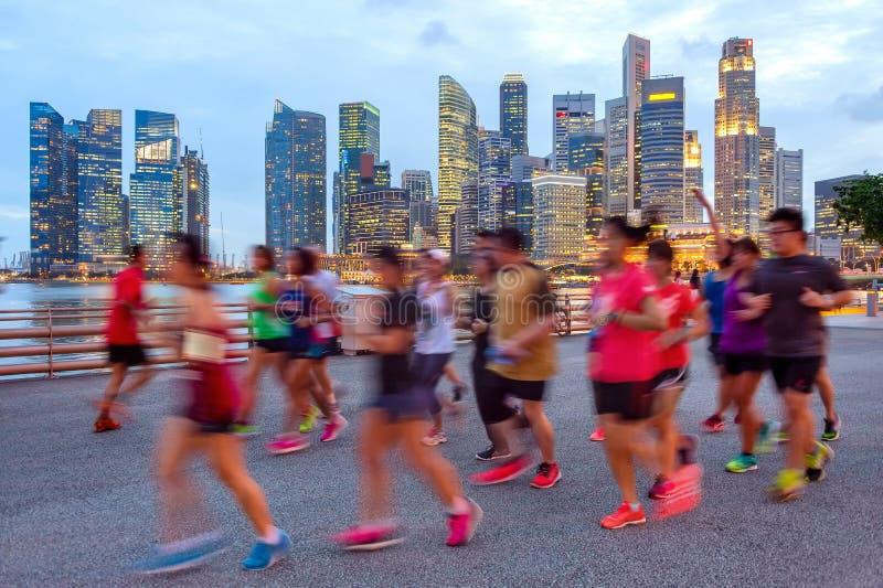 Joggers på upplyst Singapore promenad royaltyfri fotografi