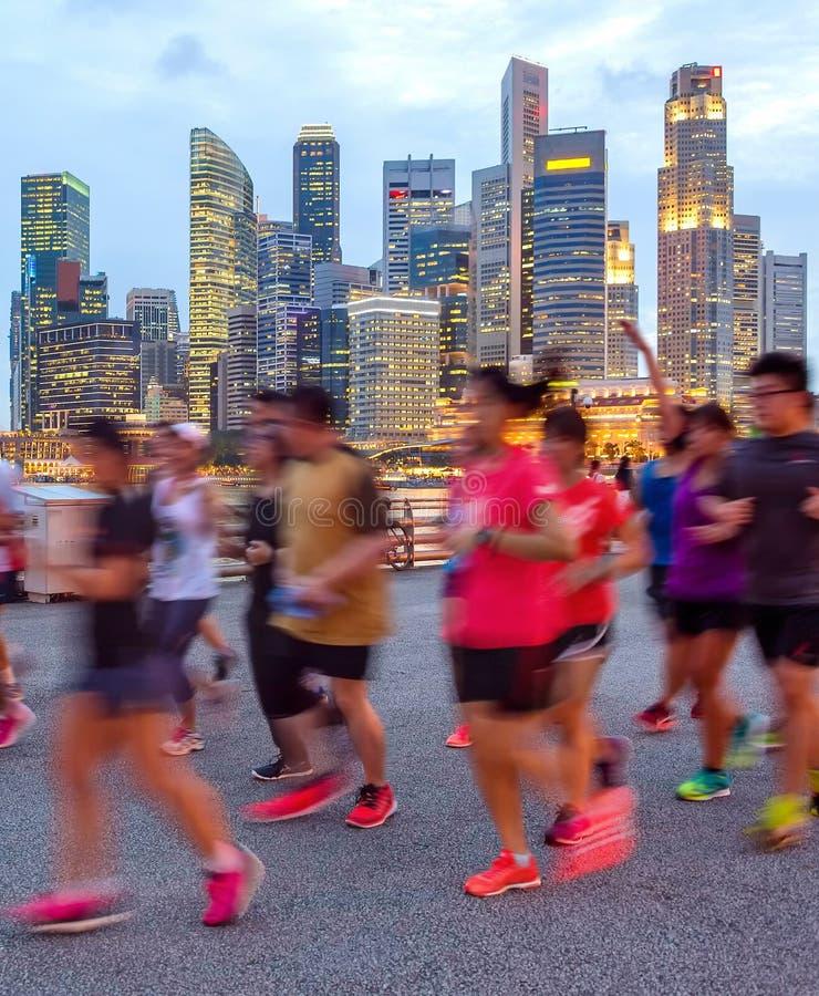 Joggers på upplyst Singapore promenad royaltyfri bild