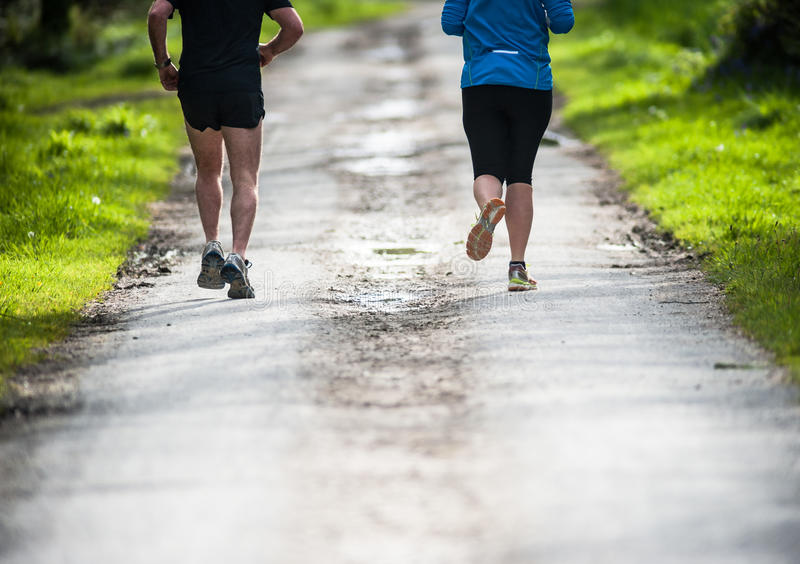 Joggers running through a park path royalty free stock photos