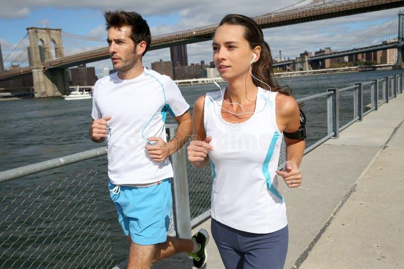 Joggers som kör förbi Hudson River royaltyfri fotografi