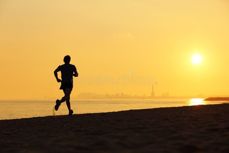 Joggersilhouet die op het strand bij zonsondergang lopen royalty-vrije stock foto's