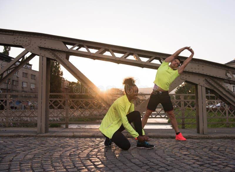 Jogging пары нагревая и протягивая в городе стоковое изображение rf