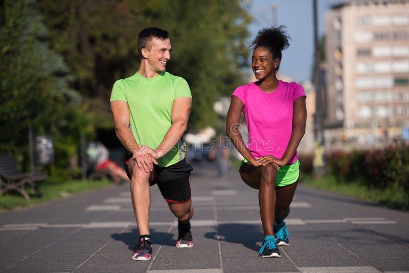 Jogging пары нагревая и протягивая в городе стоковые изображения rf