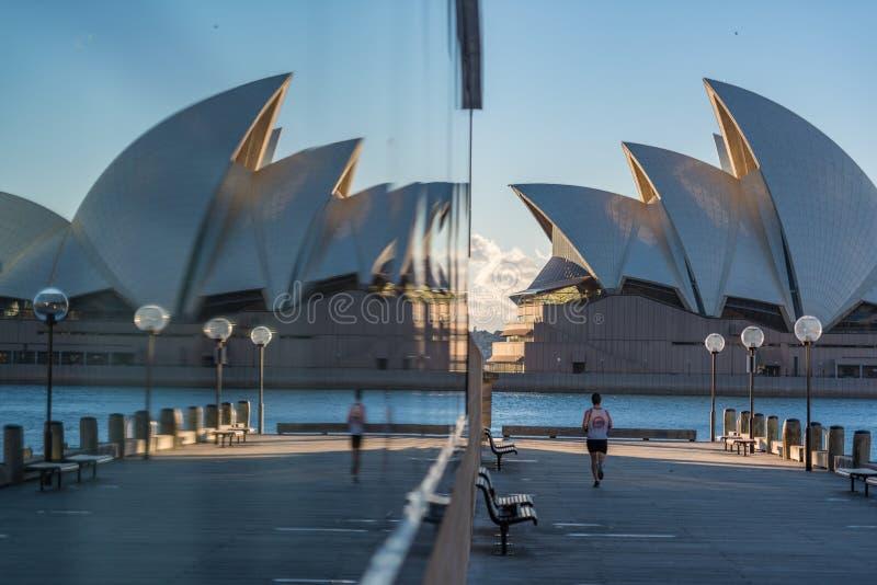 Jogging человека, бежать с оперным театром Сиднея на предпосылке стоковая фотография