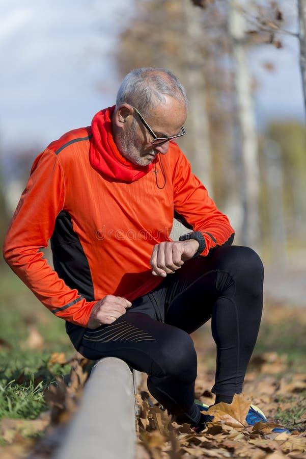 Jogging Active старший смотрящ его smartwatch стоковые изображения