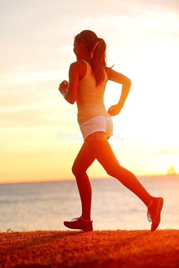 Jogging atlety kobiety bieg przy słońce zmierzchem wyrzucać na brzeg obraz royalty free