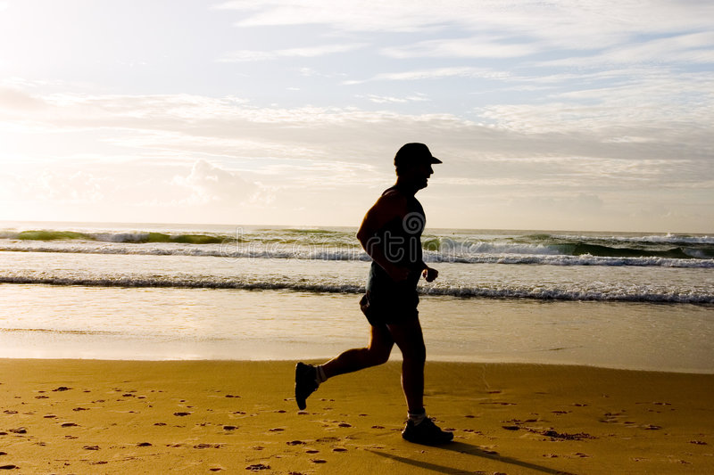 Jogging at the beach. Shot at sunrise beach royalty free stock images